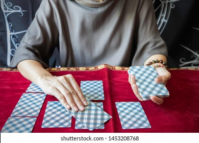 Tarot reader reading tarot cards on red tablecloth.Tarot reader hands holding tarot cards.Celtic cross card spreads on table. Fortune teller reading  and  forecasting concept.