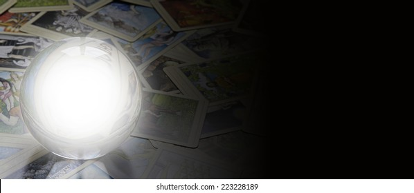 Tarot reader's website banner  -  Crystal ball with empty center laid on random scattered tarot cards fading into black on the right side forming a wide website banner
