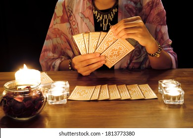 Tarot reading or fortune teller holding and picking tarot cards in her hands with burning candles and tarot cards spreading on a wooden table.Divination or forecasting concept.