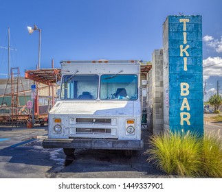 TARPON SPRINGS, FLORIDA - JUNE 30, 2019: Tarpon Springs, Florida. Funny concept for a tiki bar. Tiki Bar sign next to a beat up old white ice cream truck.