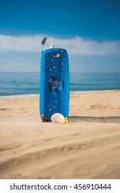 "Tarragona, Spain - 06/21/2016. Blue suitcase ""Samsonite"" on the beach Miami Platja."