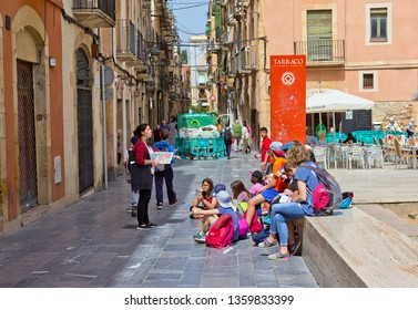Tarragona, Spain - April 25, 2018:  Teacher reads a history lesson for kids on a city street