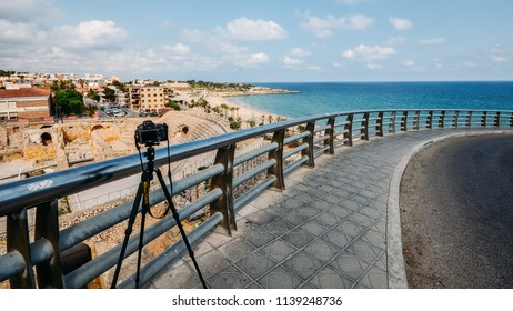 Tarragona, Spain - July 11, 2018: Illustrative editorial of Nikon D800 DSLR and tripod with panoramic view of the ancient roman amphitheater of Tarragona, Spain- UNESCO World Heritage Site Ref 875