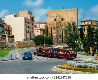 Tarragona, Spain - July 11, 2018: Tourist train passes next to open-air underground ruins of a 1st century Roman circus Tower, Tarragona, Spain