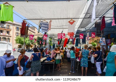 Tarragona, Spain - July 12, 2018: Shoppers at street market outlet on Rambla Nova in Tarragona selling discount clothes