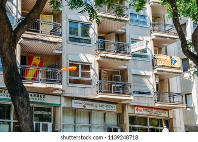 Tarragona, Spain - July 12, 2018: Spanish and Catalan flags presented on respective balconies by perhaps rival neighbours on Rambla Nova in Tarragona, Catalonia, Spain.