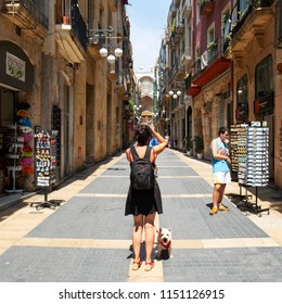 TARRAGONA, SPAIN - JULY 28, 2018: A tourist taking a picture of the Carrer Major street, in the Part Alta, the Old Town of Tarragona, Spain, with the Cathedral in the background
