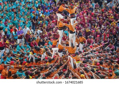 "Tarragona, Spain - October 4, 2014: Members of the ""Colla Sagals d'Osona"", build a traditional human tower at the Tarragona during celebrations in Tarraco Square Sand castle contest, October 4, 2014"
