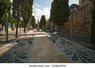 Tarragona, Spain - September, 06, 2013. People walk on Tarragona Passeig arqueologic (Archaeological Promenade). This pedestian route passes under Roman era walls