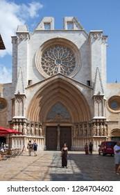Tarragona, Spain - September, 06, 2018. People walk near facade of Tarragona cathedral. This church is the main medieval landmark of the city.