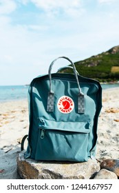 TARRAGONA, SPAIN - SEPTEMBER 16, 2018: A popular Fjallraven Kanken backpack on a rock, on a quiet beach in Tarragona, Spain. This is the best-selling product of the Swedish Fjallraven company