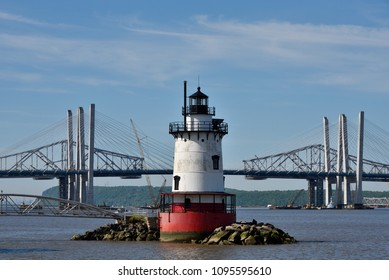 TARRYTOWN, NY - MAY 21, 2018: The Tarrytown Lighthouse is seen with both the new and old Tappan Zee Bridges in the background. The older span is being disassembled into pieces.