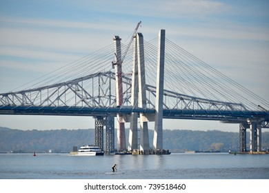 TARRYTOWN, NY - OCTOBER 22, 2017: The old and new Tappan Zee bridges western towers on a sunny day as a man is stand up paddle boarding nearby in the Hudson River.