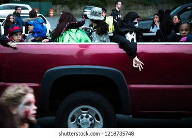 Tarrytown, NY - October 28, 2018: Child in mask makes incendiary racist hand gesture over the side of truck in parade.