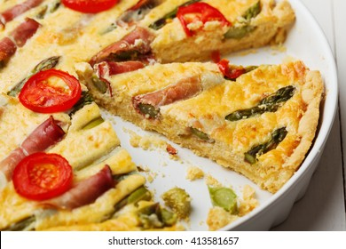 Tart with asparagus and tomatoes on white wooden background.
