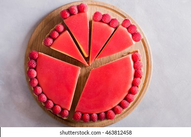 Tart cake with jellied and fresh raspberry on the light concrete background.  Top view