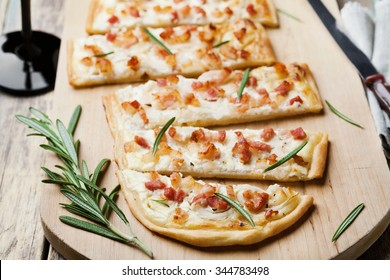 Tart Flambe or Flammkuchen on wooden cutting board, traditional Alsatian pie, rustic style