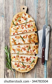 Tart Flambe or Flammkuchen on wooden cutting board, traditional Alsatian pie, rustic style, top view.