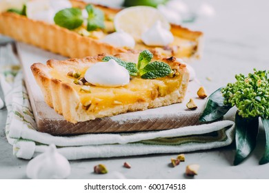 Tart with lime and lemon curd, nut pistachios and meringue on stone gray table. Citrus cake. Horizontal image with copy space
