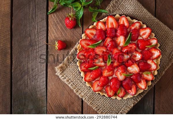 Tarte aux fraises et crème fouettée décorée de feuilles de menthe. Vue supérieure