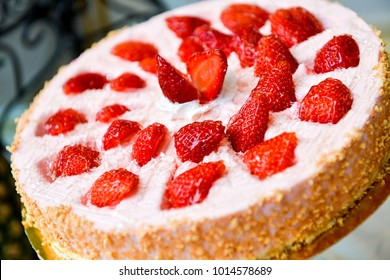 Tart with strawberries and whipped cream on table