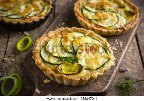 tart with zucchini, leek and cheese on rustic background