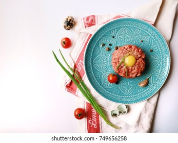 Tartar raw fresh minced meat with quail egg, cherry tomatoes, garlic and pepper mix. Gourmet eating.  Closeup.