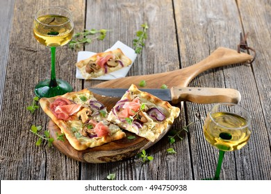 Tarte Flambee from Alsace with sour cream, onions, mushrooms and serrano ham, served with local Alsatian wine