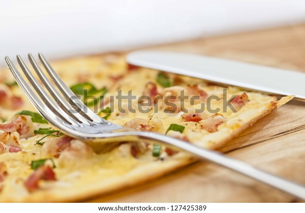 Tarte flambee with fork on wooden