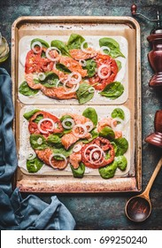 Tarte flambee with salmon , spinach and tomatoes , cooking preparation on rustic kitchen table background, top view