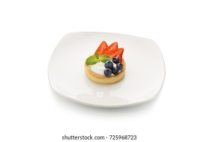 tartlet with cream and strawberries and blueberries on a white background