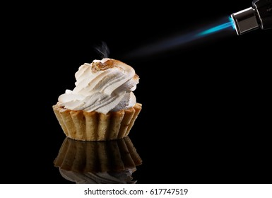 Tartlet with a meringue and kitchen torch /  blowtorch with blue flame isolated on black background. Funny sweets.