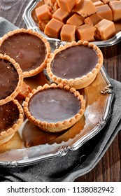 tartlets with chocolate filling close-up and toffee caramel pieces on silver vintage plate decorated with linen napkin on wooden table background