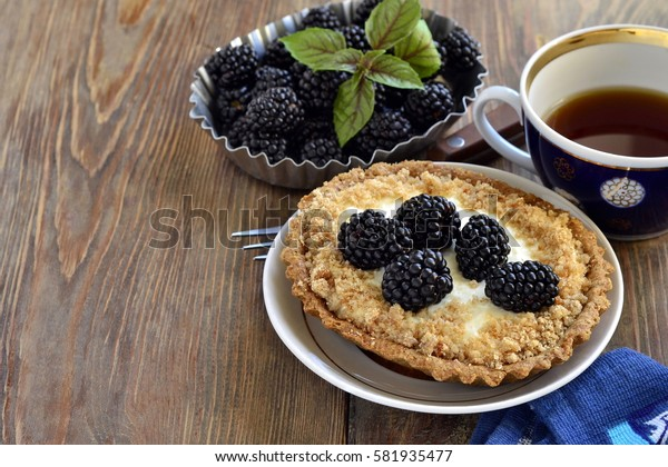 Tartlets with cream and blackberries, copy space