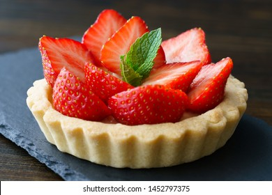 Tartlets with custard, strawberries and mint served on a slate plate. Dark wooden table, high resolution