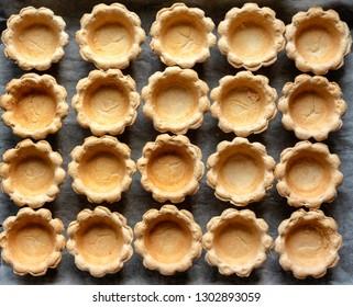 Tartlets empty in many rows on a baking sheet
