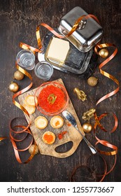 Tartlets with red caviar, champagne and butter on a festive table. Traditional Russian Christmas or New Year's holiday table. Top view. Space for text.