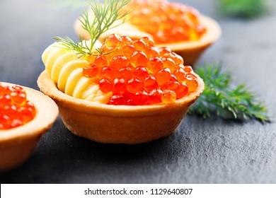 Tartlets with red caviar close up. Gourmet food close up, appetizer. Close-up salmon caviar. Delicatessen. Gourmet food. Texture of caviar. Seafood.