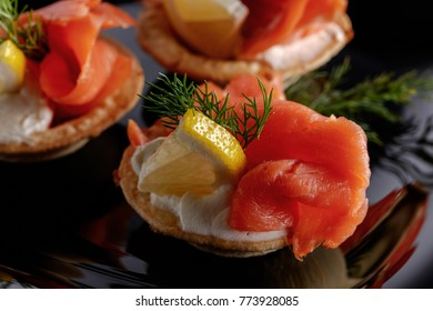 Tartlets with salmon , cream and a slice of lemon on a black plate.