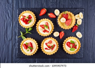 tartlets with strawberries, banana slices loaded with whipped custard cream  - diplomat on a black slate plate, view from above, close-up