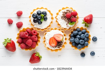 Tartlets (tarts, open pastry pies) with ricotta cheese (cottage cheese) and fresh berries (straberry, raspberry and blueberry). Healthy dessert breakfast, snack, morning table. White wooden background