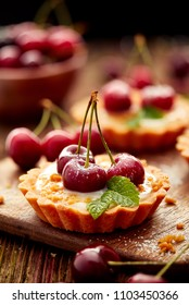Tarts with fresh cherries and vanilla custard and caramel, delicious dessert on a wooden table, close up