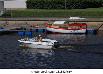 Tartu, Estonia / July 08, 2019: A family with three children makes a boat trip on a motor boat. Two girls sunbathe on the pier.
