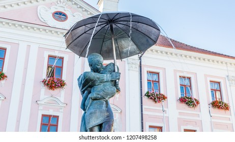 Tartu, Estonia - September 27, 2018: Sculpture of kissing studens under an umbrella in front of the town hall of Tartu in Estonia