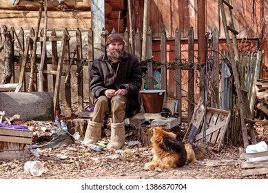 Tarusa, Kaluga region, Russia,-  April 19, 2019. Old collapsing wooden house and rubbish, man and dog in the street in front of the house.