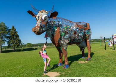 Tarusa, Russia - June 5, 2019: One girl picks up another to ring a bell hanging on the neck of a cow sculpture
