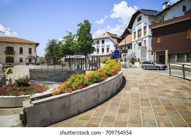 TARVISIO ITALY - JUNE 24 2016: Tarvisio downtown square with flowers, trees and hotels in a sunny day with clouds. Tarvisio, Italy.
