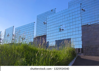 Tashkent, Uzbekistan - 28 April 2018: Heliostatic field against bright blue sky. Solar sensor in center of heliostats' mirrors to direct reflected sun rays to solar concentrator.