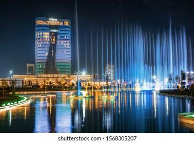 Tashkent, Uzbekistan - 30 October, 2019: beautiful dancing fountain illuminated at night with reflection in pond in new Tashkent City Park