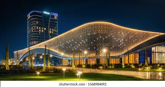 Tashkent, Uzbekistan - 30 October, 2019: Congress hall and Hilton hotel with colorful illumination at night in Tashkent City Park
